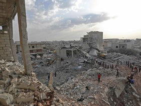 Syrians gather amidst destruction in Zardana, in the mostly rebel-held northern Syrian Idlib province, in the aftermath of following air strikes in the area late on June 8, 2018