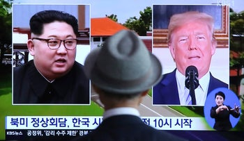 A man watches a TV screen showing file footage of Donald Trump and Kim Jong Un in South Korea, June 11, 2018.