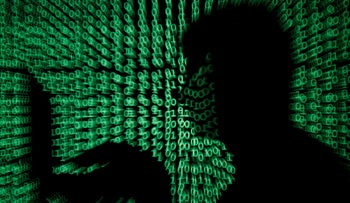 A man holds a laptop computer as cyber code is projected on him in this illustration picture taken on May 13, 2017