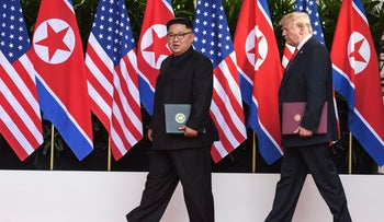 North Korea leader Kim Jong Un and U.S. President Donald Trump walk with the documents they just signed at the Capella resort on Sentosa Island Tuesday, June 12, 2018 in Singapore.