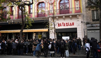 People stand in front of the Bataclan concert venue during ceremonies across Paris marking the terror attacks in 2015, November 13, 2017.