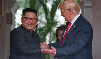 This handout photo taken on June 12, 2018 and released by The Straits Times shows North Korea's leader Kim Jong Un (L) shaking hands with US President Donald Trump (R) as they meet for the historic US-North Korea summit, at the Capella Hotel on Sentosa island in Singapore.