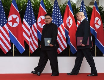 TOPSHOT - US President Donald Trump (R) walks out with North Korea's leader Kim Jong Un (L) after taking part in a signing ceremony at the end of their historic US-North Korea summit, at the Capella Hotel on Sentosa island in Singapore on June 12, 2018