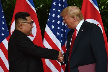 North Korea's leader Kim Jong Un shaking hands with U.S. President Donald Trump at the end of their historic summit in Singapore on June 12, 2018.