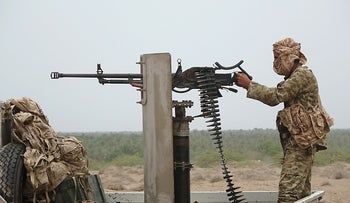 A Pro-government Yemeni soldier fires a machine gun near the city of Al Jah in the Hodeida province, 50 kilometres from the port city of Hodeida, June 7, 2018.