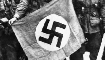 American paratroopers proudly display a Nazi flag captured shortly after they made a successful landing behind the German lines on the Normandy coast of France on June 9, 1944