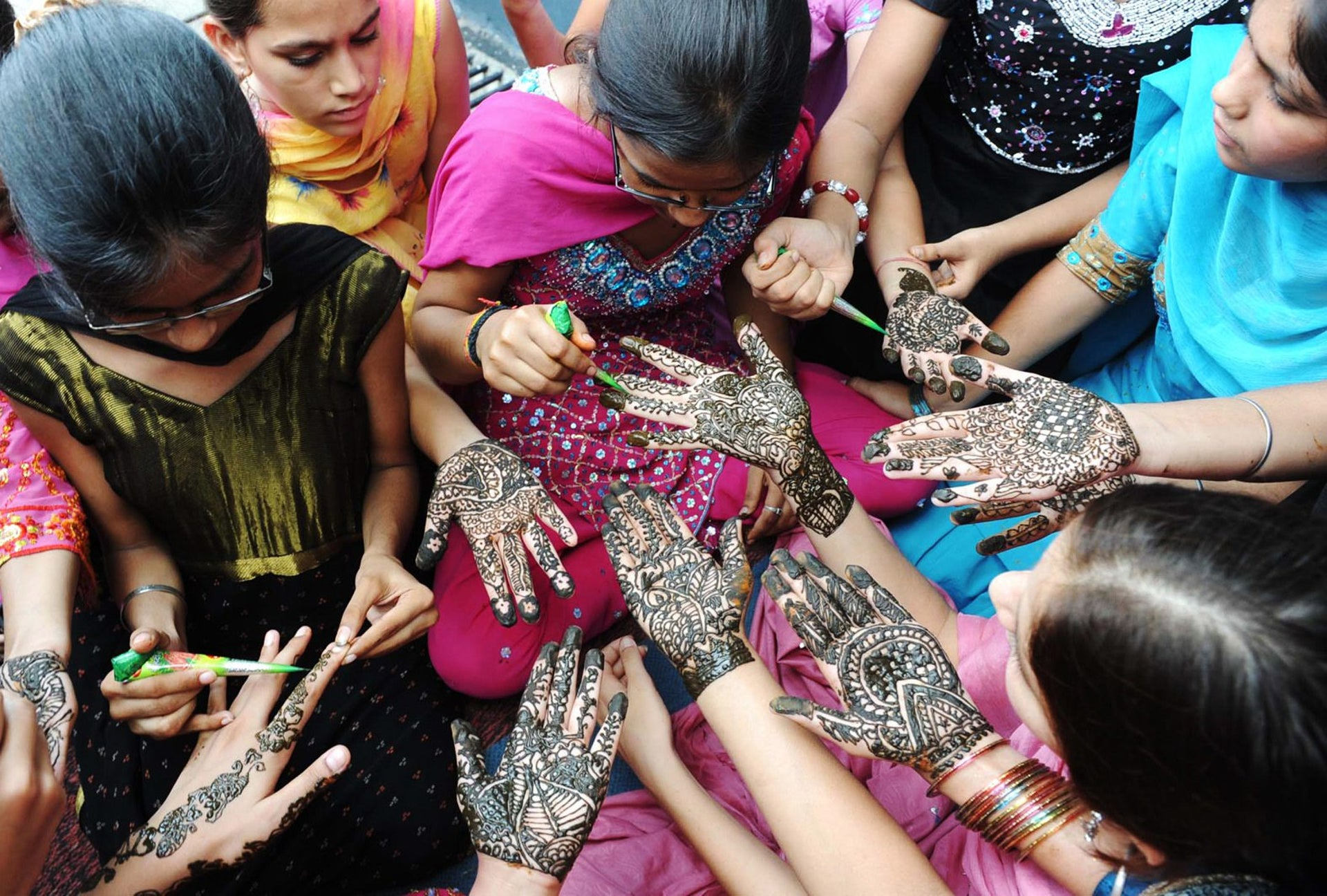 Indian schoolgirls decorate each other's hands with henna during Teej festival celebrations in Amritsar on July 25, 2009.