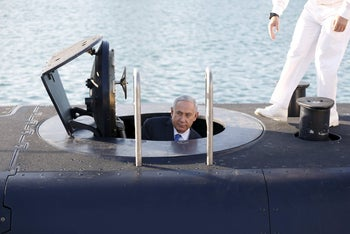 File photo: Israeli Prime Minister Benjamin Netanyahu climbs out after a visit inside the Rahav submarine, after it arrived in Haifa port, January 12, 2016.