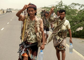 Yemeni pro-government forces flash the victory gesture as they arrive in al-Durayhimi district, about nine kilometres south of Hodeidah international airport on June 13, 2018.