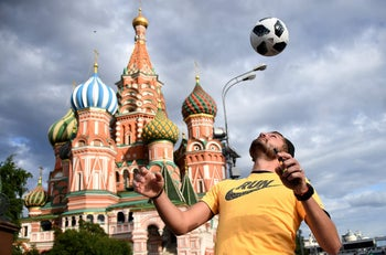 A man joggles with a ball in front the Saint Basil's Cathedral on the Red Square in Moscow on June 9, 2018