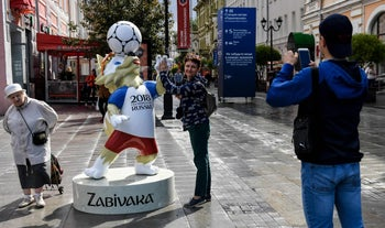 People take a picture in front of a Zabivaka, the official mascot for  Russia 2018 football World Cup, in Nizhny Novgorod, on June 13, 2018