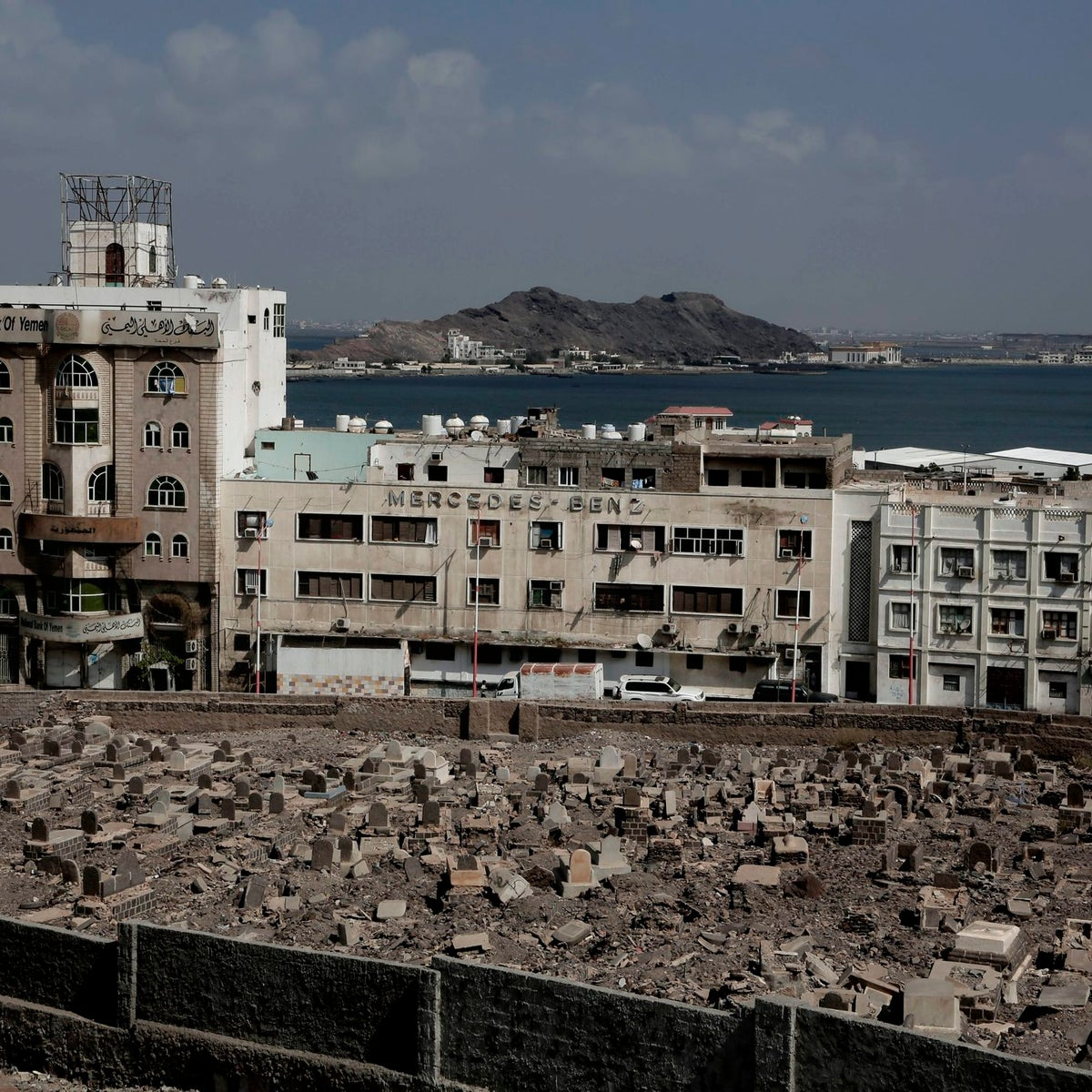 This Feb. 17, 2018, photo shows the Mercedes Benz building damaged in Aden, Yemen. Once a peg in a thriving commercial center that sprang up under colonial rule, the dealership sits empty and pockmarked with bullet holes. Its damaged sign now stands over bay windows boarded up by people sheltering inside. With the war still raging, nothing is being rebuilt.
