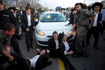 Ultra-Orthodox men clash with police as they block a highway during a protest against the detention of a member of their community who refuses to serve in the military, in Bnei Brak, Israel, March 12, 2018.