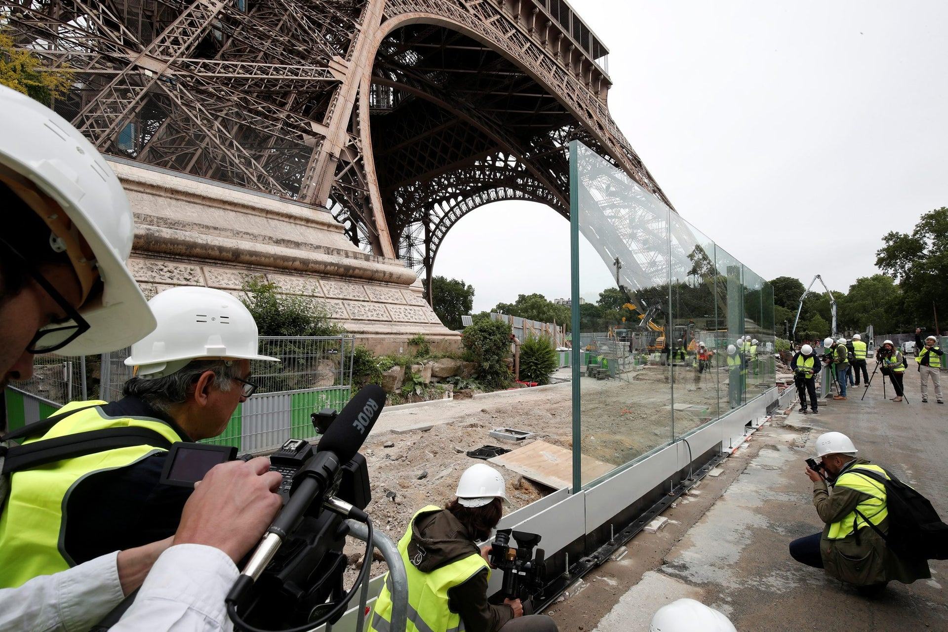 Members of the media make images of the new glass security fence which is under construction around the Eiffel Tower in Paris, France, June 14, 2018.