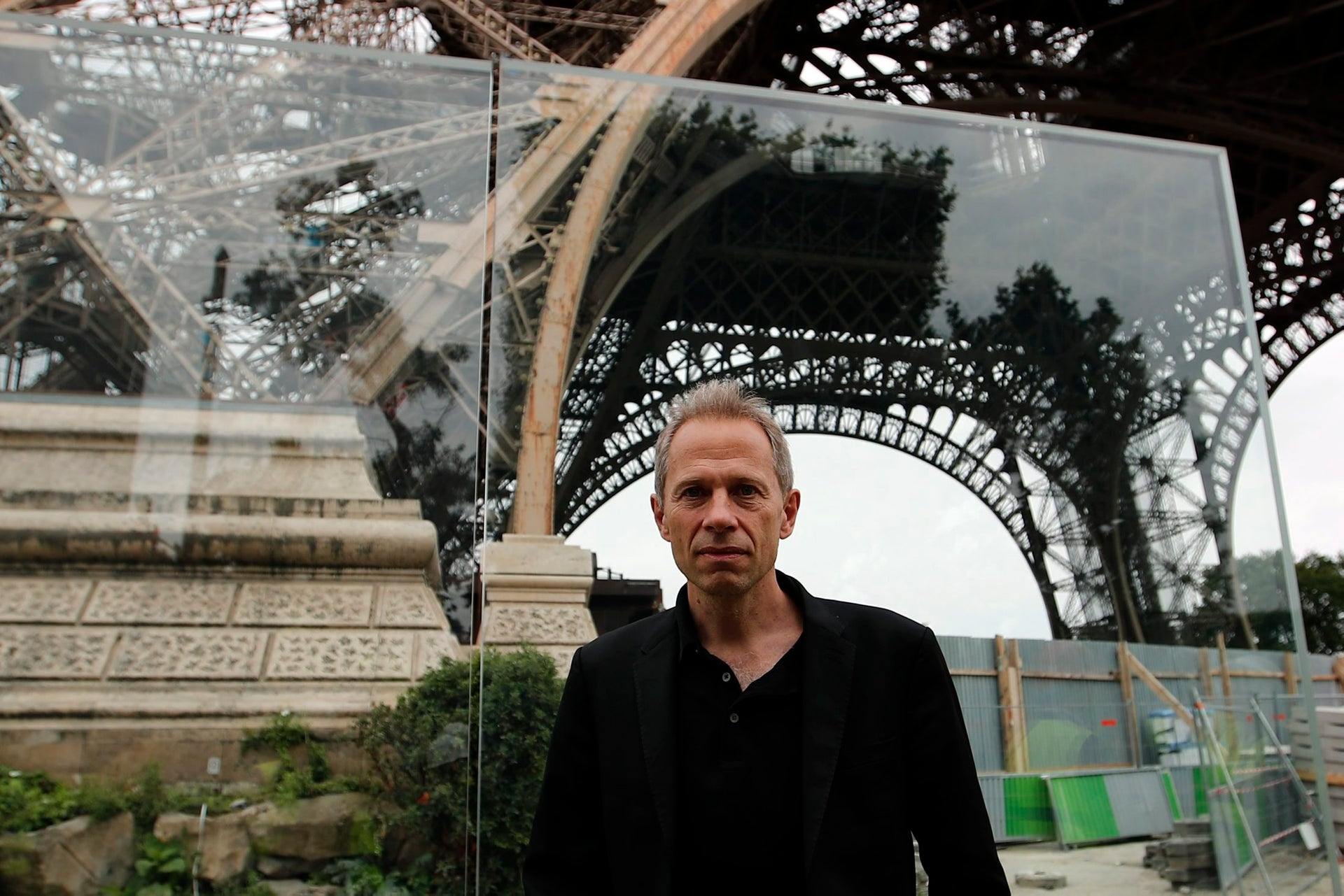 Architect Dietmar Feichtinger poses in front of a new security bulletproof glass barrier under construction around the Eiffel Tower in Paris, France, Thursday, June 14, 2018.