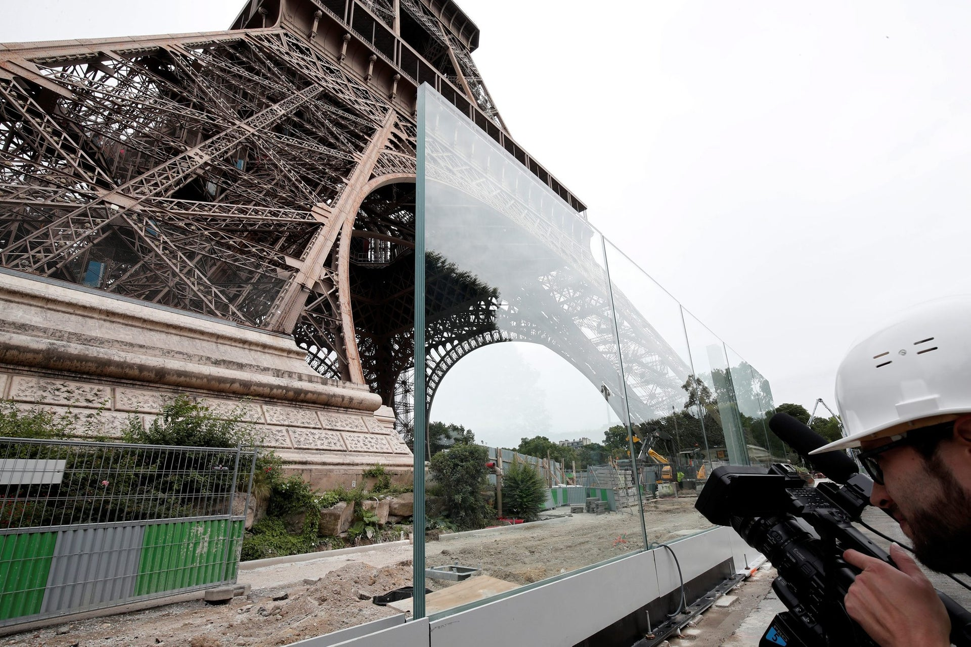 A member of the media makes images of the new glass security fence which is under construction around the Eiffel Tower in Paris, France, June 14, 2018.