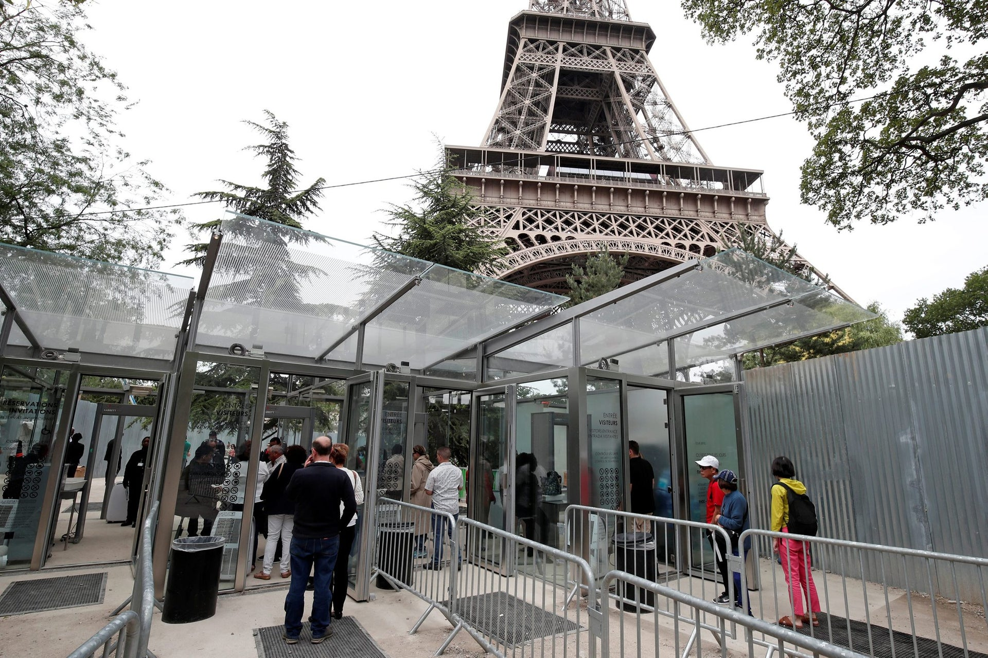 Tourists and visitors queue to pass the security check at the entrance to the new glass fence around the Eiffel Tower in Paris, France, June 14, 2018.