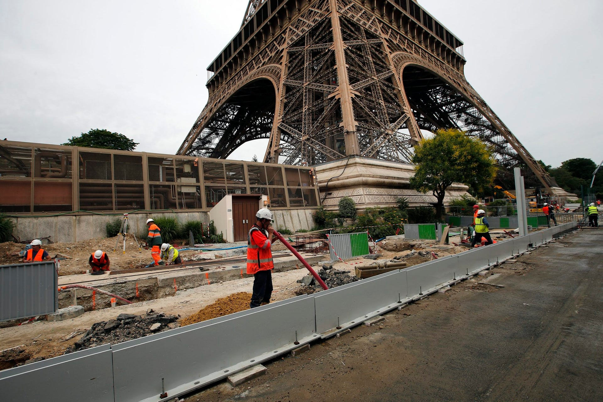 Construction workers build a new security bulletproof glass barrier under construction around the Eiffel Tower in Paris, France, Thursday, June 14, 2018. Paris authorities have started replacing the metal security fencing around the Eiffel Tower with a more visually appealing glass wall. The company operating the monument said see-through panels are being set up instead of the fences at the north and south of the famed monument that were installed for the Euro 2016 soccer event. Each panel is 3 meters high, over 6 centimeters thick and weighs 1.5 ton.