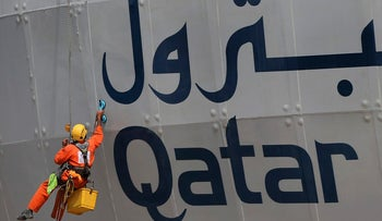 In this May 5, 2018 photo, a worker cleans the exterior of the Qatar Petroleum building in Doha, Qatar. Saudi Arabia, Egypt, the United Arab Emirates and Bahrain severed diplomatic ties and cut air, ground and sea links to Qatar over its alleged support of terrorist groups and its warm relations with Iran. But Qatarג€™s massive natural gas reserves and close ties with other countries in the region have allowed it to weather the crisis, and daily life has gone on largely unchanged. (AP Photo/Kamran Jebreili)
