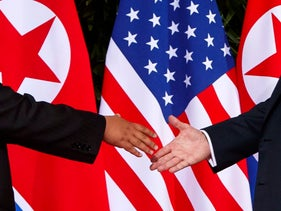 U.S. President Donald Trump, right, reaches to shake hands with North Korea leader Kim Jong Un at the Capella resort on Sentosa Island in Singapore.