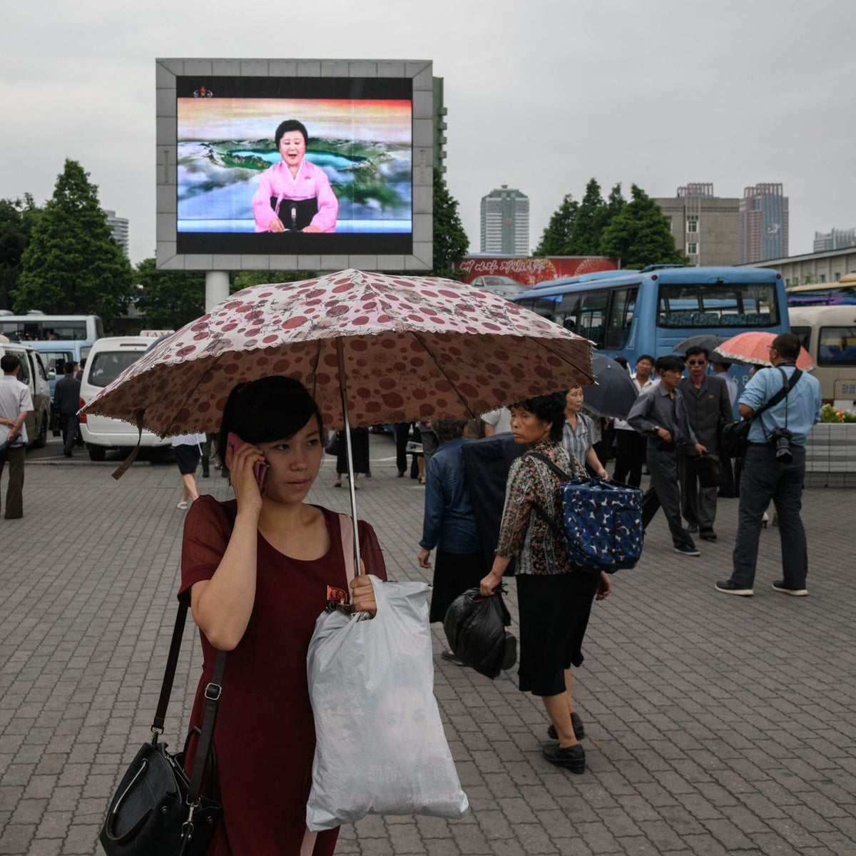 People watch a news broadcast on a giant television screen outside the central railway station in Pyongyang on June 13, 2018.