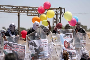 Palestinian protesters prepare kites loaded with flammable material to be flown toward Israel, al-Bureij, central Gaza Strip, June 14, 2018.