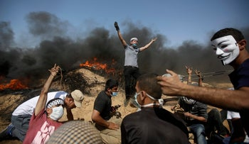 Palestinians take cover near the Gaza Strip's border with Israel during a protest east of Khan Younis, in the Gaza Strip, June 8, 2018.