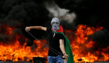 A Palestinian demonstrator holds a sling during a protest marking the 70th anniversary of Nakba, near the Jewish settlement of Beit El, West Bank, May 15, 2018.