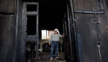 The Dawabshe house in the village of Duma after the arson attack in 2015 that killed an 18-month-old  Palestinian child; his parents succumbed to their injuries after some weeks and only a four-year-old boy ultimately survived. The picture shows a man wearing a keffiyah standing inside the charred house. Friday, July 31, 2015.
