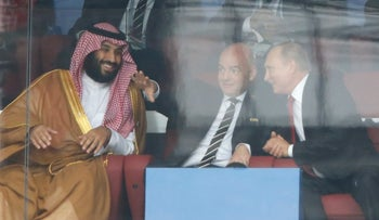 Saudi Crown Prince Mohammed bin Salman, left, FIFA President Gianni Infantino and Russian President Vladimir Putin watching the match between Russia and Saudi Arabia at the 2018 soccer World Cup in Moscow, June 14, 2018.