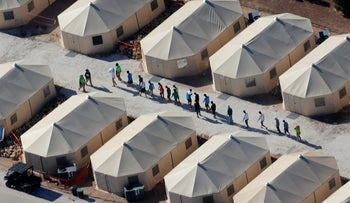 """Immigrant children in a tent encampment under the new """"zero tolerance"""" policy by the Trump administration walking in single file at the facility near the Mexican border in Tornillo, Texas, U.S. June 19, 2018"""