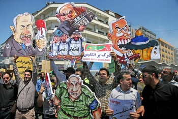 Iranian protesters hold up caricatures of leaders of Israel during the annual anti-Israeli Al-Quds, Jerusalem, Day rally in Tehran, Iran, Friday, June 8, 2018.