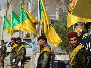 Members of the Iraqi Hezbollah Brigades carry flags during a ceremony in Baghdad on June 21, 2018, commemorating fellow members who were killed in air strikes 4 days earlier.