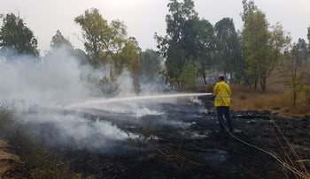 Firefighters trying to put out fires caused by flaming balloons launched at Israel from Gaza on June 23, 2018.