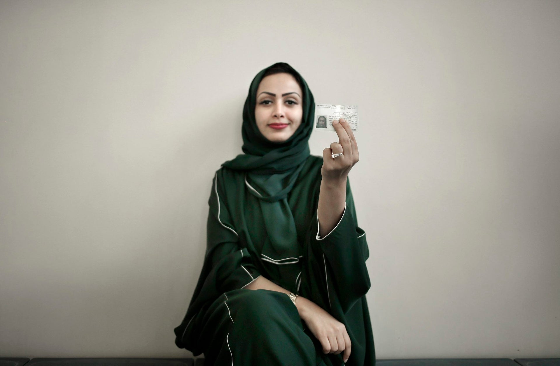 In this June 23, 2018 photo, 34-year old Asmaa al-Assdmi poses for a photograph holding her new car license at the Saudi Driving School inside Princess Nora University in Saudi Arabia.