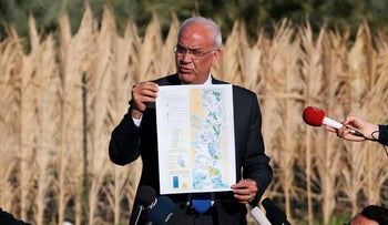 Palestinian chief negotiator Saeb Erekat holds a map as he speaks to media about an Israeli plan to appropriate land, Jericho, West Bank, January 20, 2016.