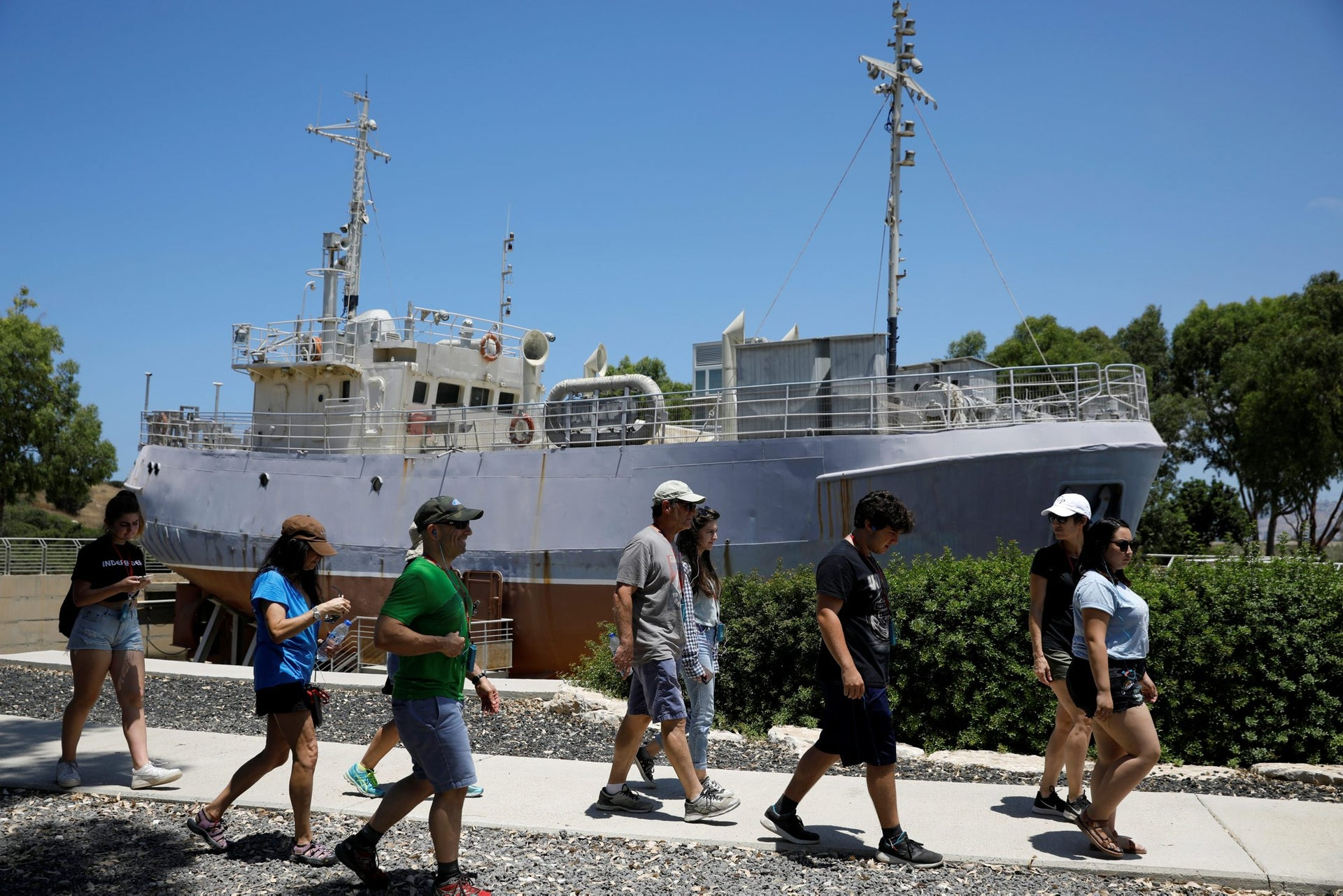 Tourists walk past an original ship used to illegally bring Jewish immigrants, at the former British detention camp of Atlit, currently operated as a museum by the Council for Conservation of Heritage Sites in Israel, June 19, 2018. Picture taken June 19, 2018.