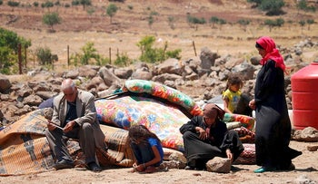 Displaced Syrian from the Daraa province fleeing shellings by pro-government forces wait in a makeshift camp in the province of Quneitra, southwestern Syria, near the border with the Israeli-occupied Golan Heights, on June 22, 2018