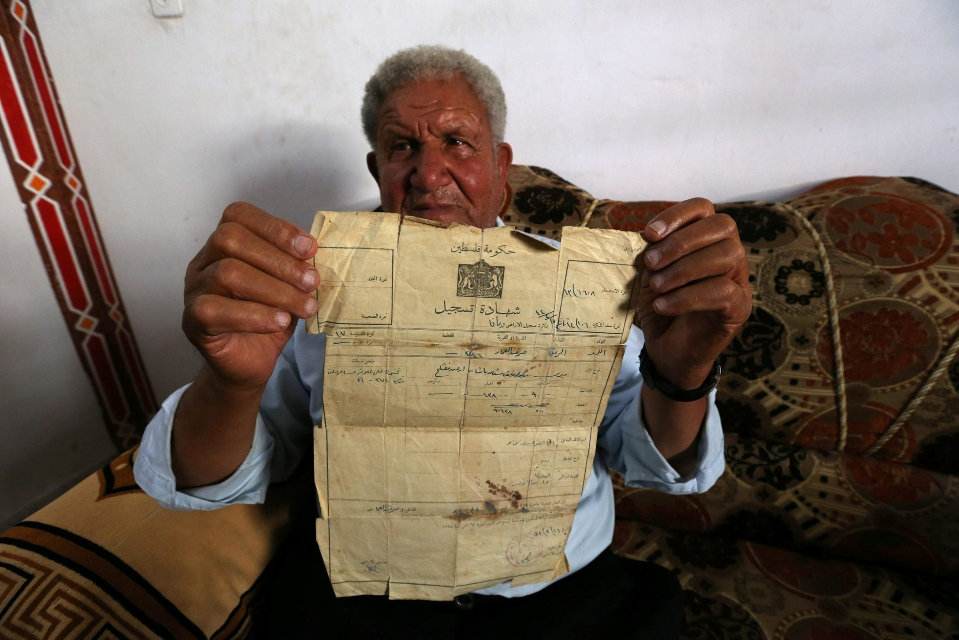 Palestinian Ahmed Jarghoun, 75, displays a land registration certificate from the British era, in Khan Younis in the southern Gaza Strip June 18, 2018. Picture taken June 18, 2018.