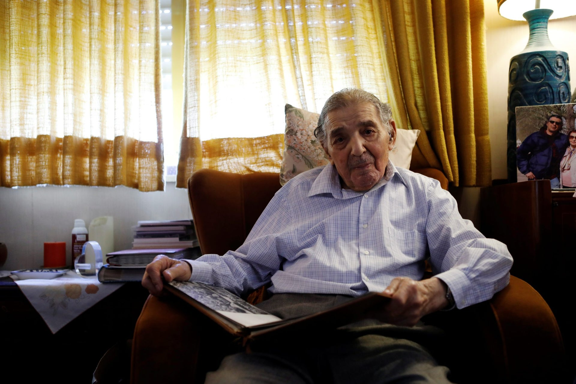 Ram Haviv, 93, who served in the British army between 1943-1946, holds a photo album during an interview in his home in Jerusalem, June 14, 2018. Picture taken June 14, 2018.