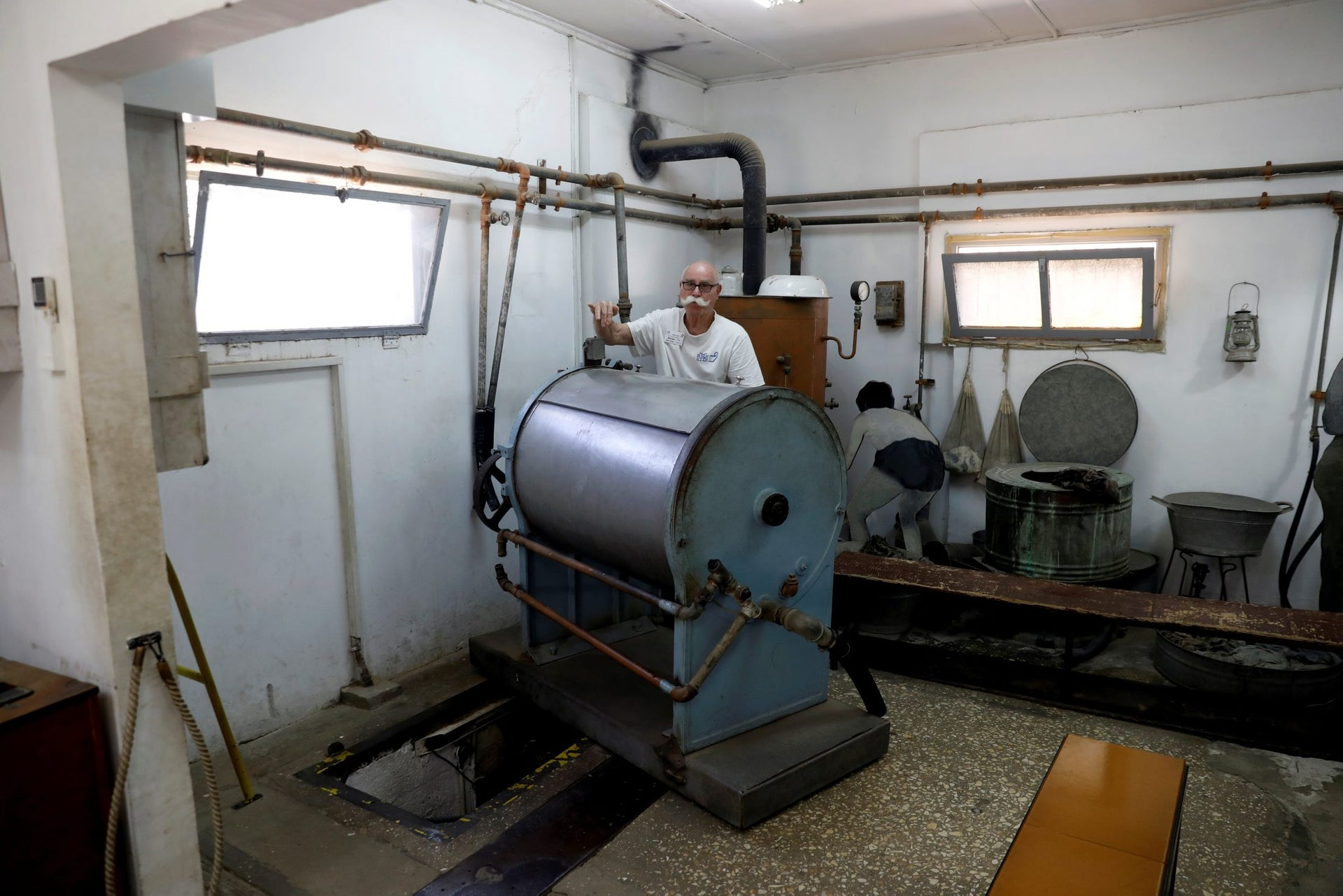 A man stands next to an industrial washing machine which hides one of the entrances to the Ayalon Institute, a factory for the production of 9mm bullets for the Sten submachine gun that was secretly built in 1945 by Jewish paramilitary group Hahagana during the British Mandate, in Rehovot, Israel, June 14, 2018.