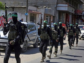Masked militants from the Izzedine al-Qassam Brigades, a military wing of Hamas, march with their weapons, during a large-scale drill across the Gaza strip. March 25, 2018