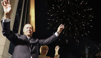 Turkish President Tayyip Erdogan and his wife Emine Erdogan greeting supporters gathered above a balcony at the headquarters of the AK Party in Ankara, June 24, 2018.