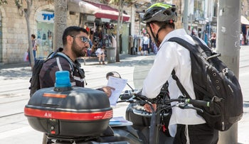 A cyclist in Jerusalem receives a citation from a police officer on Jaffa Road, June 2018.