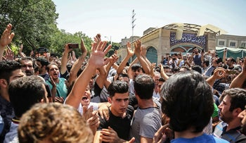 A group of protesters chant slogans at the main gate of old grand bazaar in Tehran, Iran, June 25, 2018.