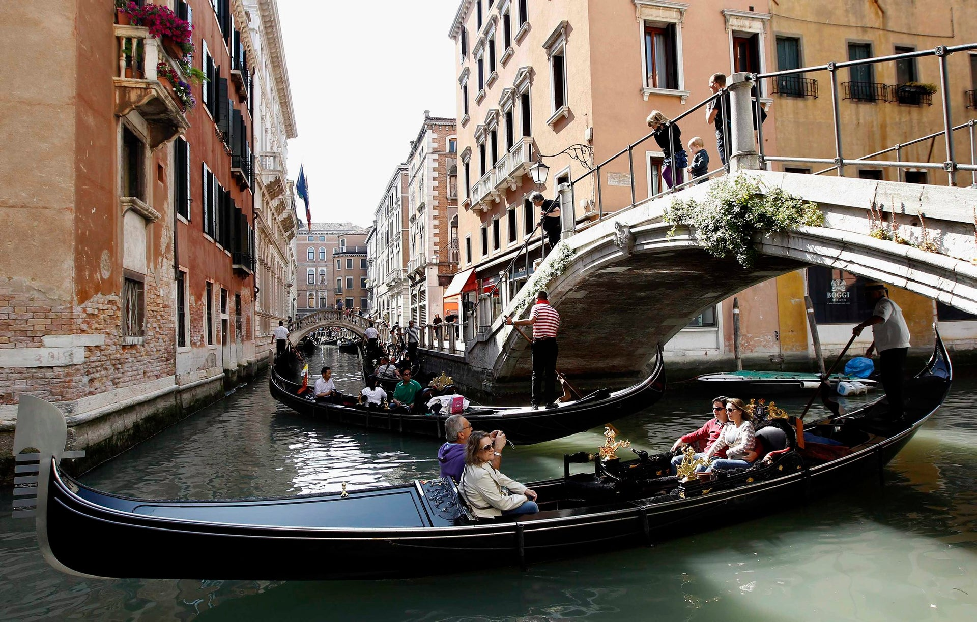 Gondoliers row gondolas with tourists in a canal in Venice.