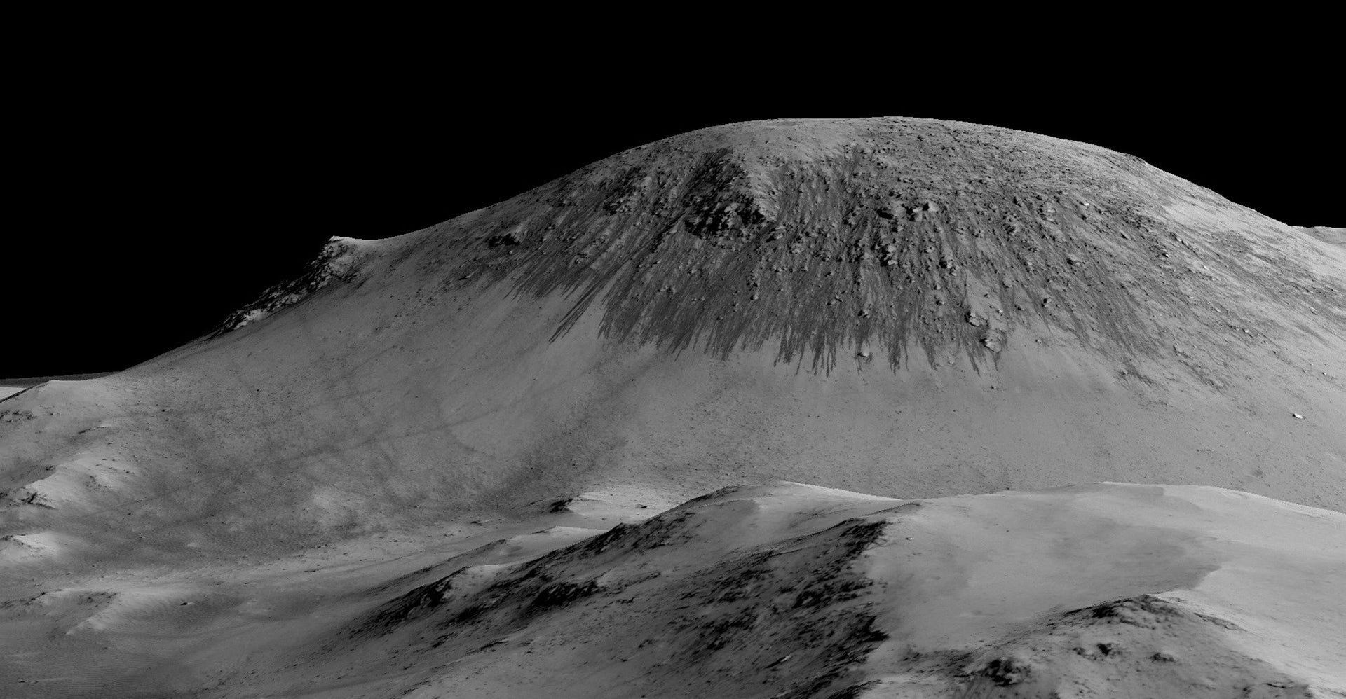 A handout image made available by NASA on September 27, 2015, shows dark, narrow, 100 meter-long streaks called recurring slope lineae flowing downhill on Mars are inferred to have been formed by contemporary flowing water.