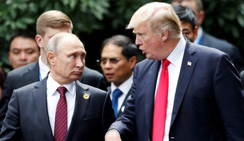 U.S. President Donald Trump and Russia's President Vladimir Putin talk during the family photo session at the APEC Summit in Danang, Vietnam November 11, 2017