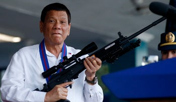 Philippine President Rodrigo Duterte holds an Israeli-made Galil rifle in Quezon, Philippines, April 19, 2018