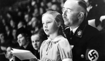 In this March 6, 1938 file photo top Nazi Heinrich Himmler, with his daughter Gudrun on his lap, watch an indoor sports display in Berlin.